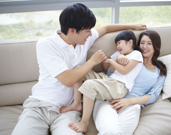 Japanese couple with young child on couch with smile